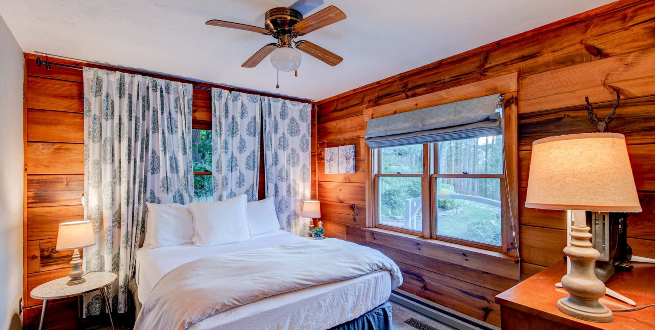 Bright bedroom with ceiling fan in the Raspberry Hill Cabin