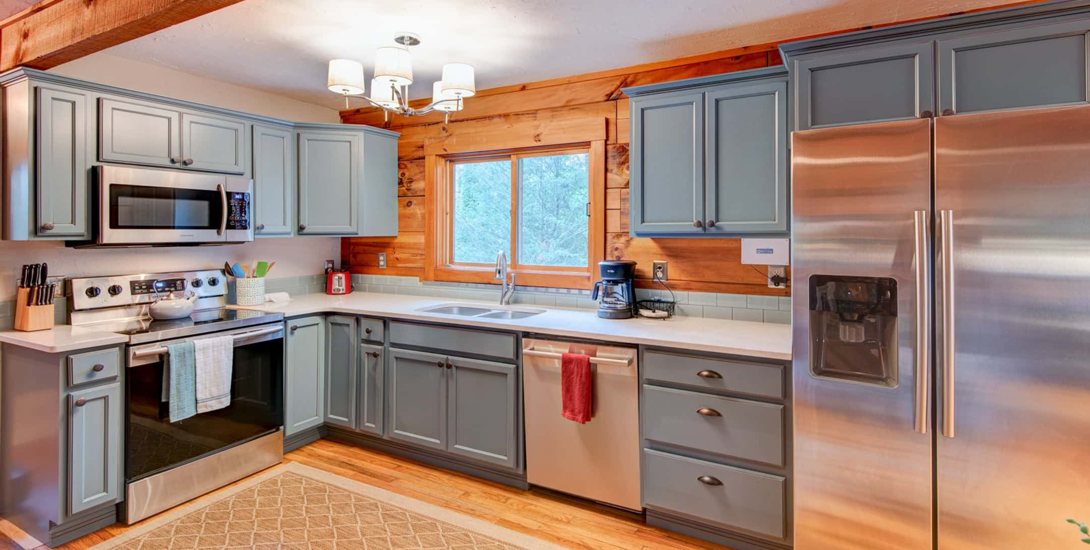 Full kitchen with range, dishwasher and hardwood floors in the Raspberry Hill Cabin