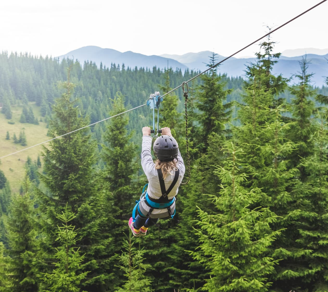 Woman on a zipline with a pine forest in the background