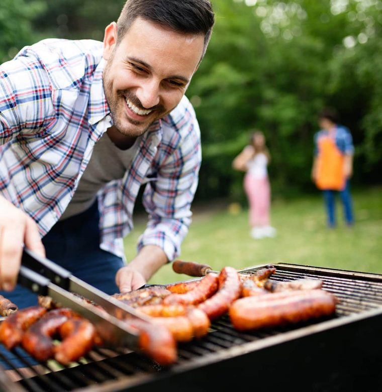 Man grilling food with family in background